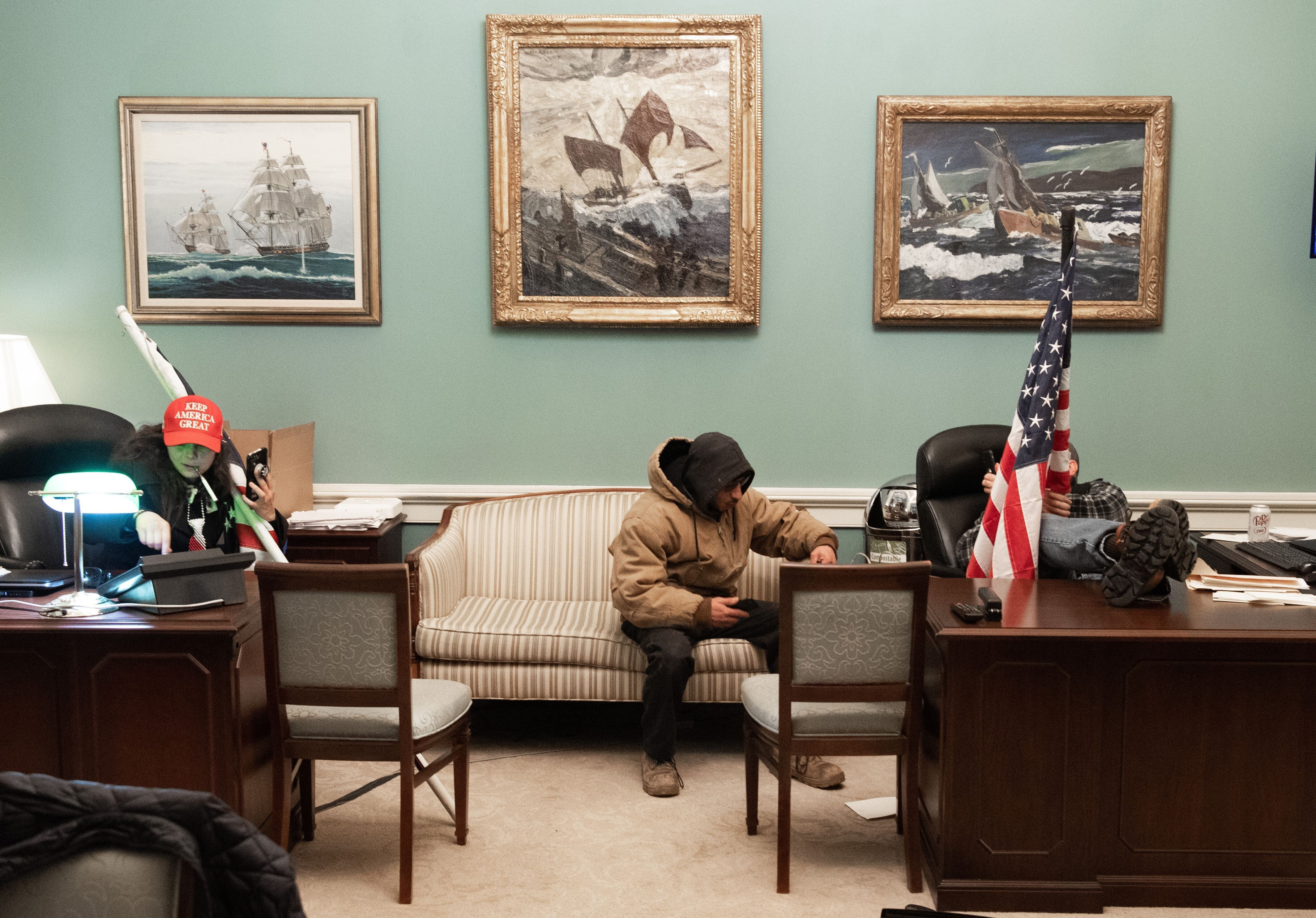 Intruders holding American flags invade Pelosi's office suite in the U.S. Capitol.