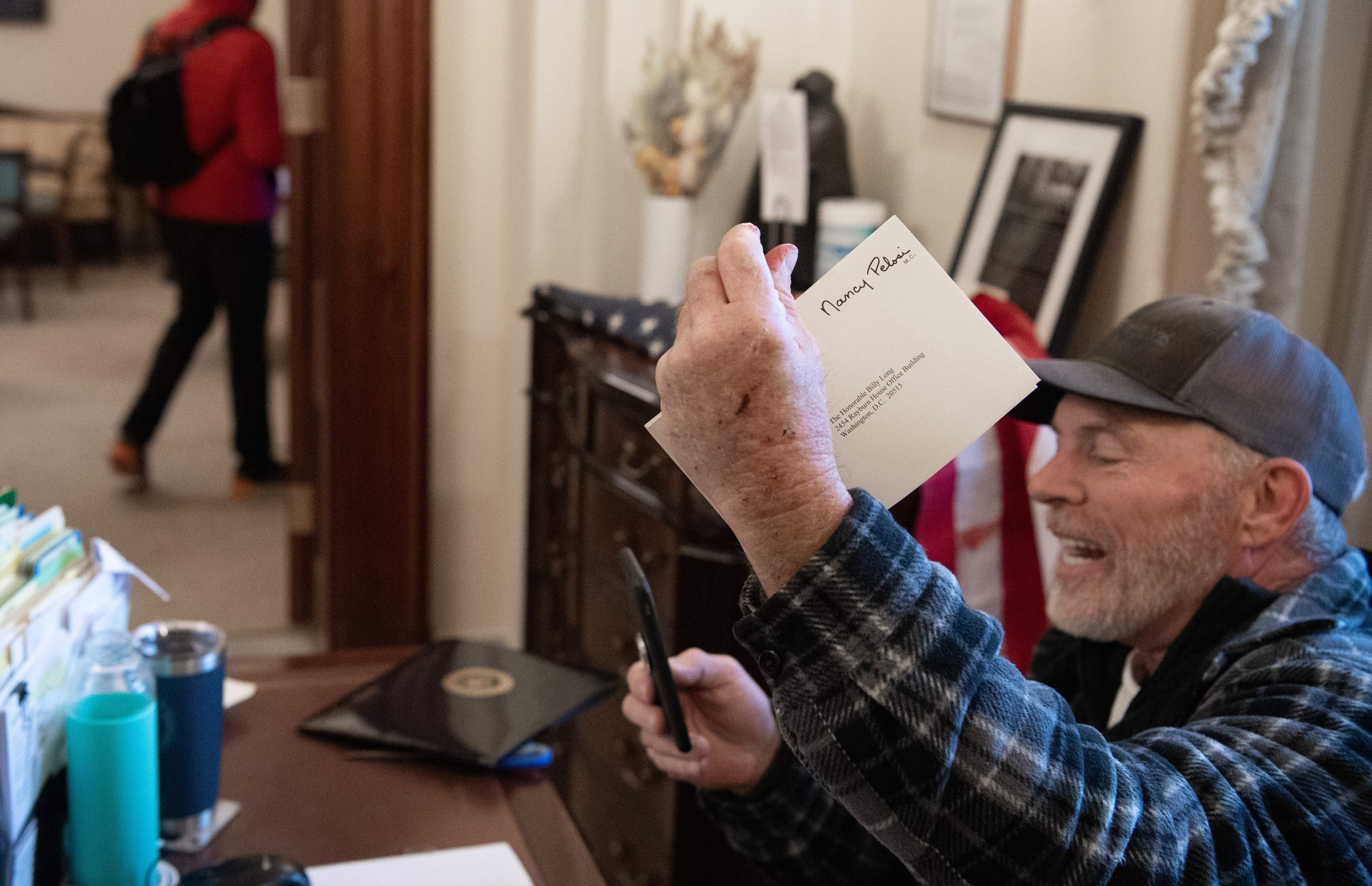 A pro-Trump rioter goes through items on the desk of a Pelosi staffer.