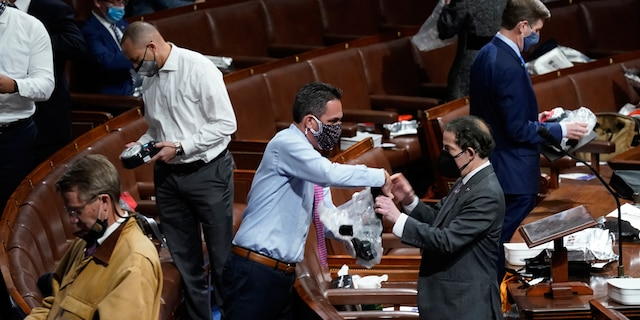 Lawmakers prepare to put on masks on the floor of the House of Representatives as protesters enter the U.S. Capitol, Wednesday, Jan 6, 2021, in Washington. (AP Photo/Andrew Harnik)