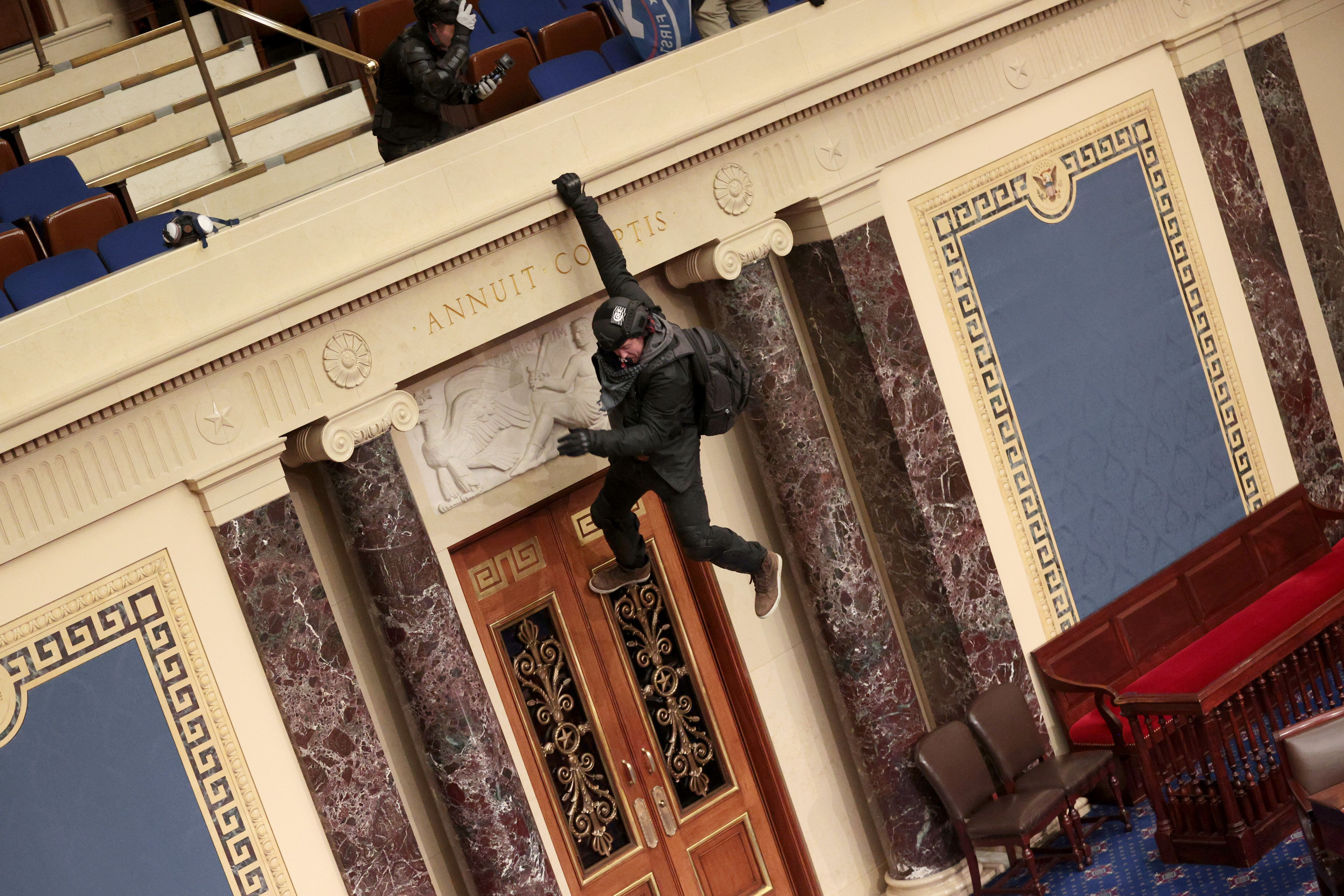 A pro-Trump protester hangs from the balcony in the Senate Chamber.