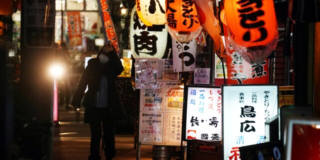 A woman wearing a face mask to help curb the spread of the new coronavirus walks through a bar street Wednesday, Jan. 6, 2021. The Japanese capital confirmed more than 1500 new coronavirus cases on Wednesday. (AP Photo/Eugene Hoshiko)