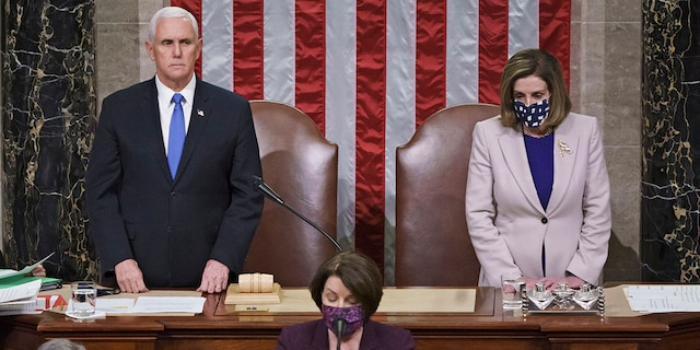 Vice President Mike Pence and Speaker of the House Nancy Pelosi, D-Calif., read the final certification of Electoral College votes cast in November's presidential election during a joint session of Congress after working through the night, at the Capitol in Washington, Thursday, Jan. 7, 2021. (AP Photo/J. Scott Applewhite, Pool)