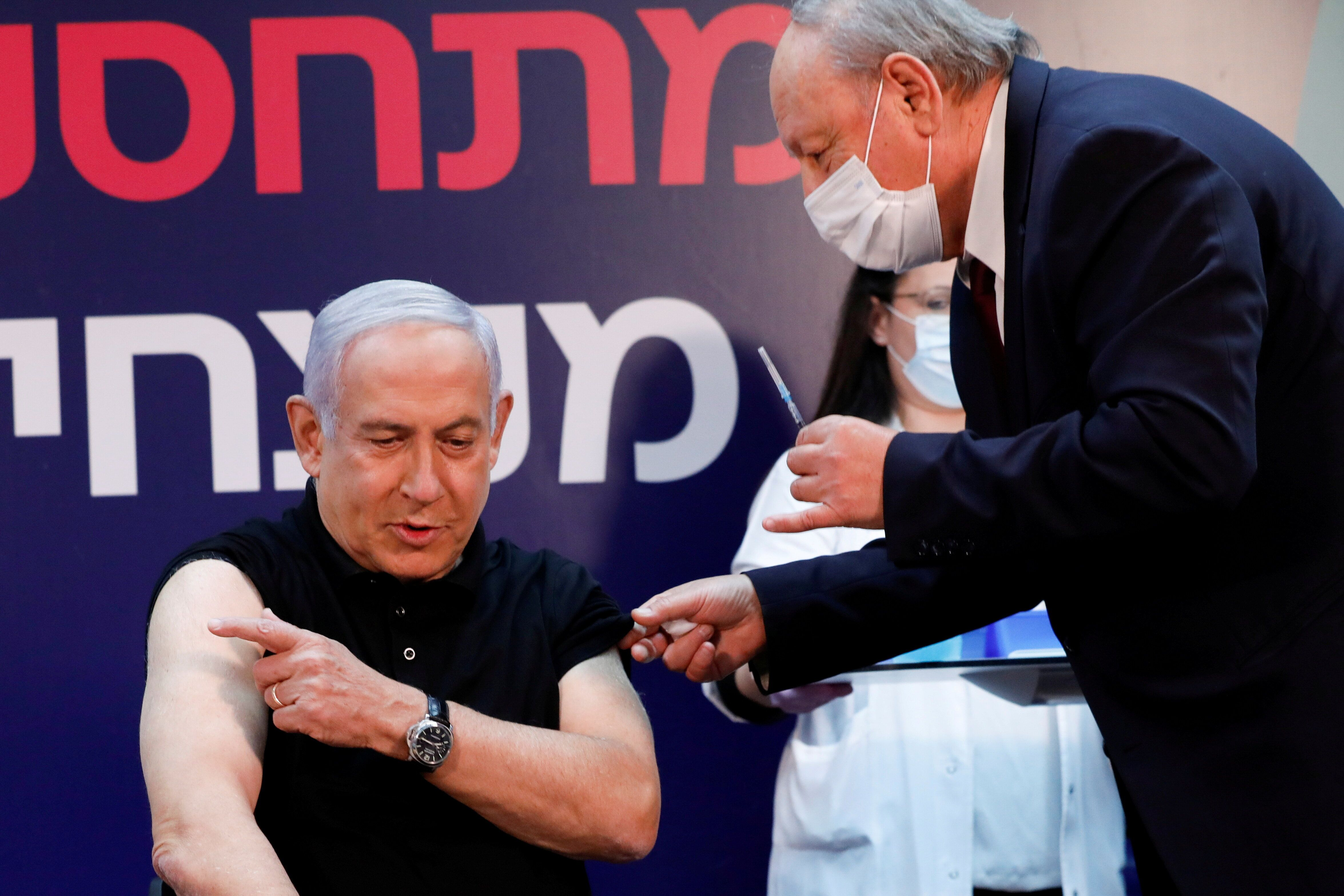 First in line: Israeli Prime Minister Benjamin Netanyahu gets ready to receive a coronavirus vaccine at Sheba Medical Center