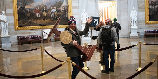 A pro-Trump protester carries the lectern of U.S. Speaker of the House Nancy Pelosi through the Roturnda of the U.S. Capitol Building after a pro-Trump mob stormed the building on January 06, 2021. (Photo by Win McNamee/Getty Images)