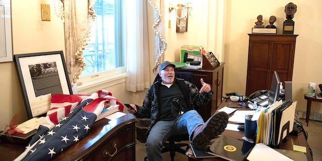 A protester sitting at House Speaker Nancy Pelosi's desk during Wednesday's siege of the U.S. Capitol has been identified as Richard Barnett. He was arrested on Friday, Jan. 8. (Photo by Saul Loeb/AFP via Getty Images)