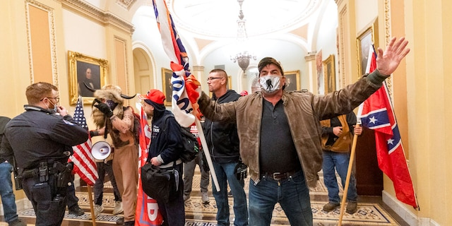 Supporters of President Donald Trump are confronted by U.S. Capitol Police officers outside the Senate Chamber inside the Capitol, Wednesday, Jan. 6, 2021 in Washington. (AP Photo/Manuel Balce Ceneta)