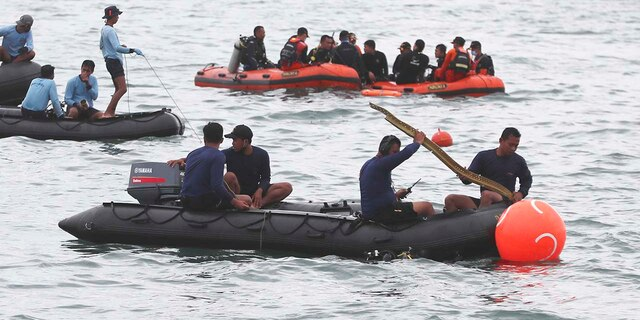 Rescuers carry debris found in the waters around the location where a Sriwijaya Air passenger jet has lost contact with air traffic controllers shortly after the takeoff, in Java Sea, near Jakarta, Indonesia, Sunday, Jan. 10, 2021. (Associated Press)