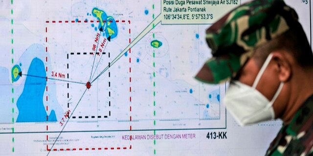 An Indonesian soldier walks past a map showing the location where a Sriwijaya Air passenger jet has lost contact with air traffic controllers shortly after taking off, at the search and rescue command center at Tanjung Priok Port in Jakarta, Indonesia, Sunday, Jan. 10, 2021. (Associated Press)