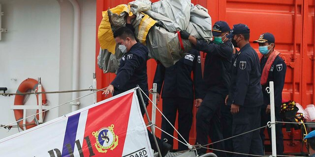 Rescuers carry debris found in the waters around the location where a Sriwijaya Air passenger jet has lost contact with air traffic controllers shortly after the takeoff, at the search and rescue command center at Tanjung Priok Port in Jakarta, Indonesia, Sunday, Jan. 10, 2021. (Associated Press)