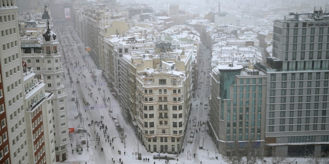 People walk during a heavy snowfall in downtown Madrid, Spain, Saturday, Jan. 9, 2021. A persistent blizzard has blanketed large parts of Spain with 50-year record levels of snow, halting traffic and leaving thousands trapped in cars or in train stations and airports that suspended all services as the snow kept falling on Saturday. (AP Photo/Andrea Comas)