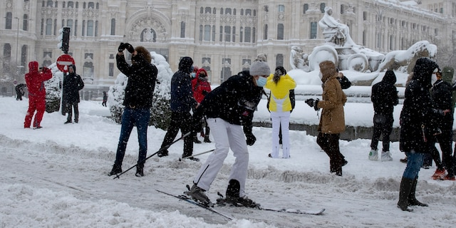 A woman skies past the Cibeles monument in front of the City Hall during a heavy snowfall in central Madrid, Spain, Saturday, Jan. 9, 2021. An unusual and persistent blizzard has blanketed large parts of Spain with snow, freezing traffic and leaving thousands trapped in cars or in train stations and airports that had suspended all services as the snow kept falling on Saturday. The capital, Madrid, and other parts of central Spain activated for the first time its red weather alert, its highest, and called in the military to rescue people from cars vehicles trapped in everything from small roads to the city's major thoroughfares. (AP Photo/Paul White)