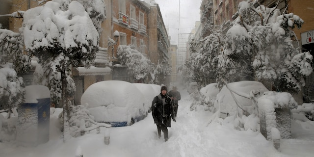 People walk during a heavy snowfall in Madrid, Spain, Saturday, Jan. 9, 2021. An unusual and persistent blizzard has blanketed large parts of Spain with snow, freezing traffic and leaving thousands trapped in cars or in train stations and airports that had suspended all services as the snow kept falling on Saturday. The capital, Madrid, and other parts of central Spain activated for the first time its red weather alert, its highest, and called in the military to rescue people from cars vehicles trapped in everything from small roads to the city's major thoroughfares. (AP Photo/Andrea Comas)