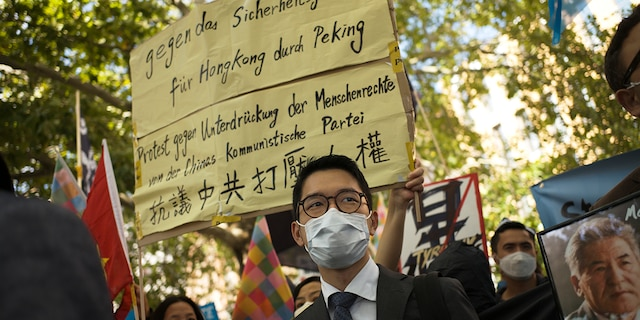 Hong Kong activist Nathan Law, center, takes part in a protest during the visit of Chinese Foreign Minister Wang Yi in Berlin, Germany, on Sept. 1, 2020. (AP Photo/Markus Schreiber, File)