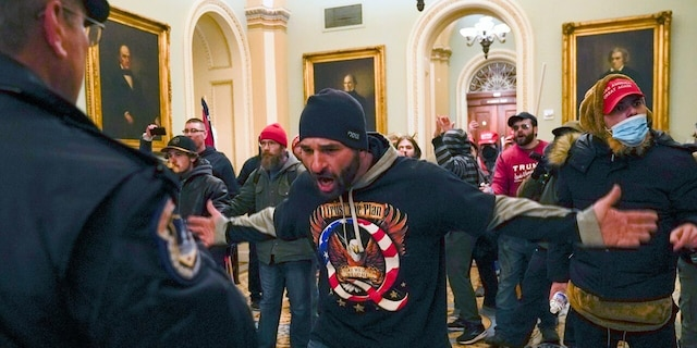 Trump supporters gesture to U.S. Capitol Police in the hallway outside of the Senate chamber after breaching the halls of the Capitol in Washington, Wednesday, Jan. 6, 2021. (AP Photo/Manuel Balce Ceneta)