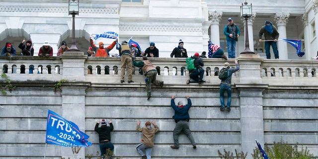 Supporters of President Trump climb the west wall of the the U.S. Capitol on Wednesday, Jan. 6, 2021, in Washington.<br> (AP Photo/Jose Luis Magana)