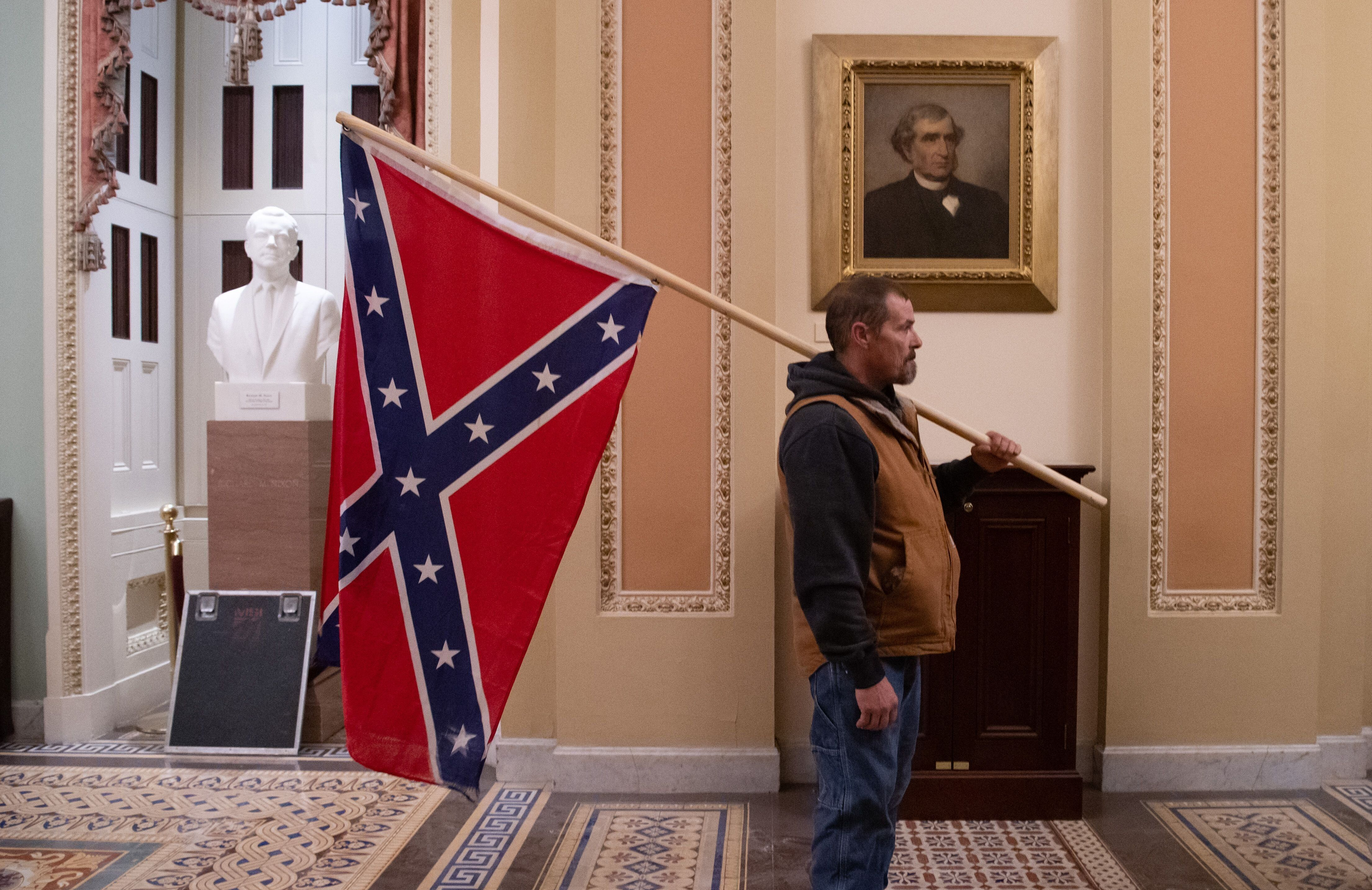 A supporter of Trump holds a Confederate flag outside the Senate Chamber during a protest after breaching the U.S. Capi