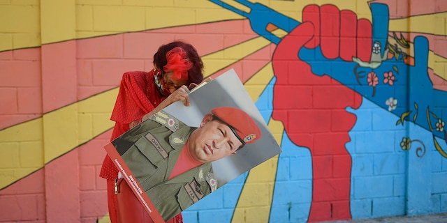 """A government supporter known as """"Caperucita,"""" or Little Red Riding Hood, holds a photo of late Venezuelan President Hugo Chavez. (AP Photo/Matias Delacroix)"""