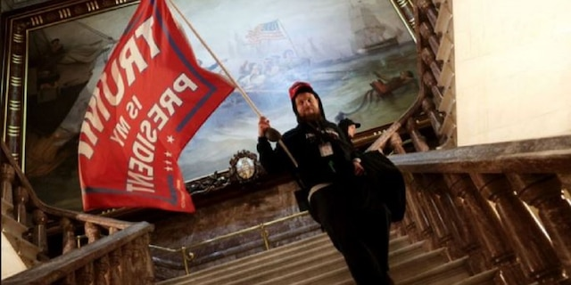 Nicholas Rodean is seen carrying a large pro-Trump flag inside the U.S. Capitol, authorities said. Rodean and six others were charged in connection with the Jan. 6 riot inside the building, the Justice Department said Wednesday.