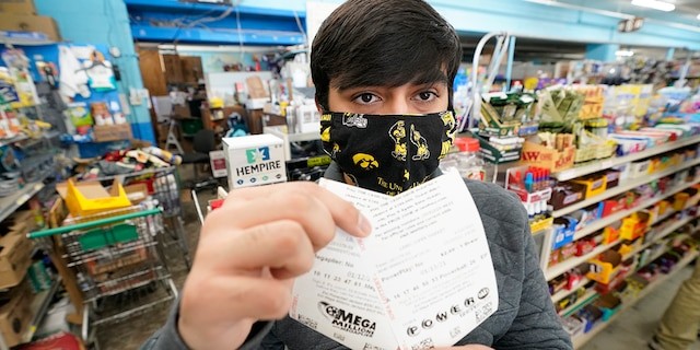 Hardik Kalra, of Des Moines, Iowa, poses for a photo with his Mega Millions and Powerball lottery tickets, Tuesday, Jan. 12, 2021, in Des Moines, Iowa. Lottery players have a chance to win the largest jackpots in nearly two years as Tuesday's Mega Millions has grown to an estimated $625 million and Wednesday's Powerball to an estimated $550 million. (AP Photo/Charlie Neibergall)