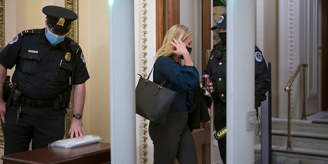 Rep. Marjorie Taylor Greene, R-Ga., an ally of President Donald Trump, passes through a metal detector before entering the House chamber, a new security measure put into place after a mob stormed the Capitol, in Washington, Tuesday, Jan. 12, 2021. (AP Photo/J. Scott Applewhite)