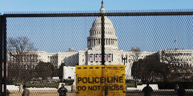 National guards are seen Wednesday, Jan. 13, 2021 on a fence that was erected to reinforce security at the Capitol in Washington. (AP Photo/Shafkat Anowar)