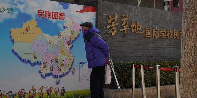 """An elderly Chinese man looks at map of Chinese showing its different ethnic groups and the slogan """"Ethnic Unity"""" in Beijing, China Monday, Jan. 11. (AP Photo/Ng Han Guan)"""