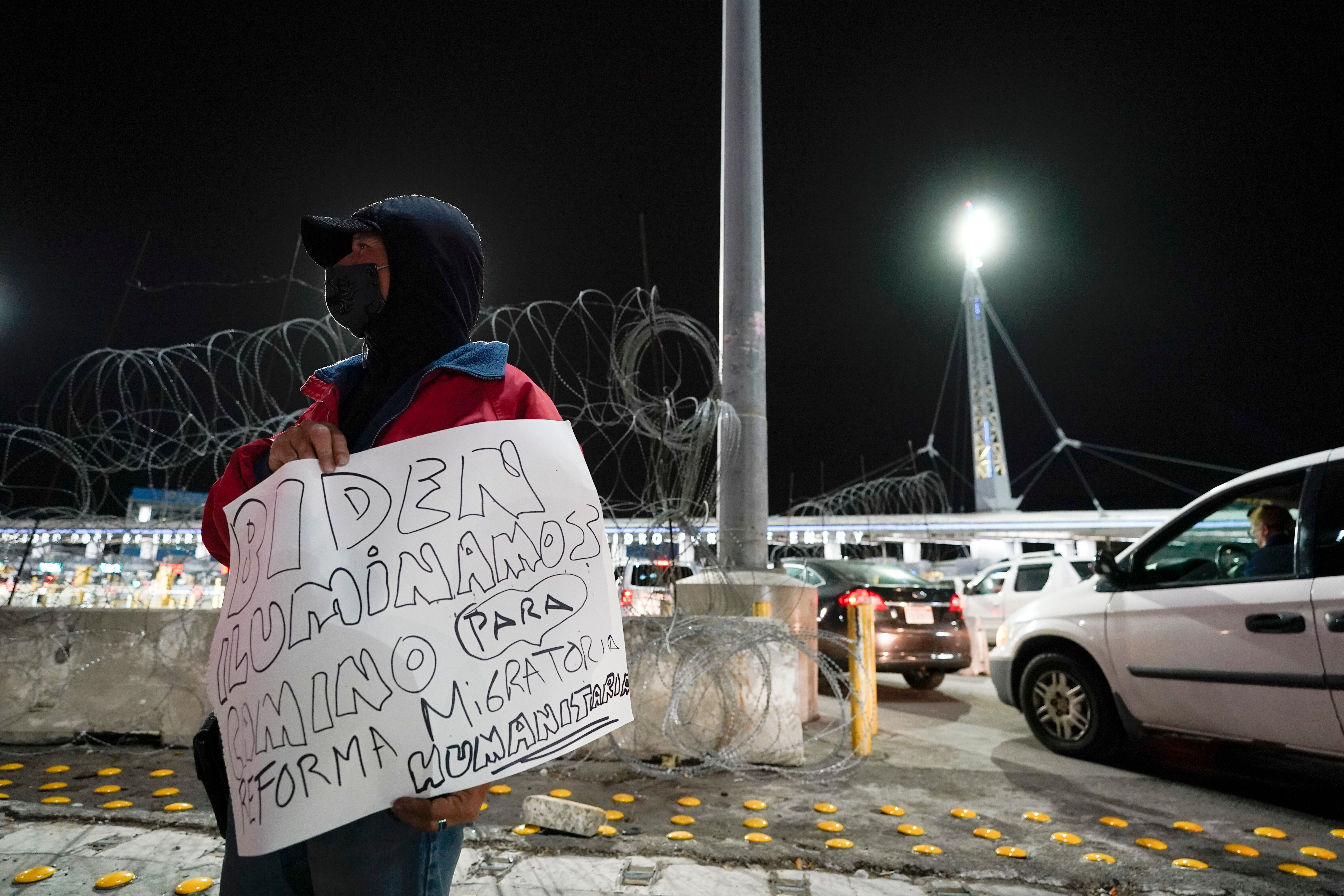 A man holds a sign during a vigil in support of migrants as he stands at the entrance to the San Ysidro Port of Entry along t