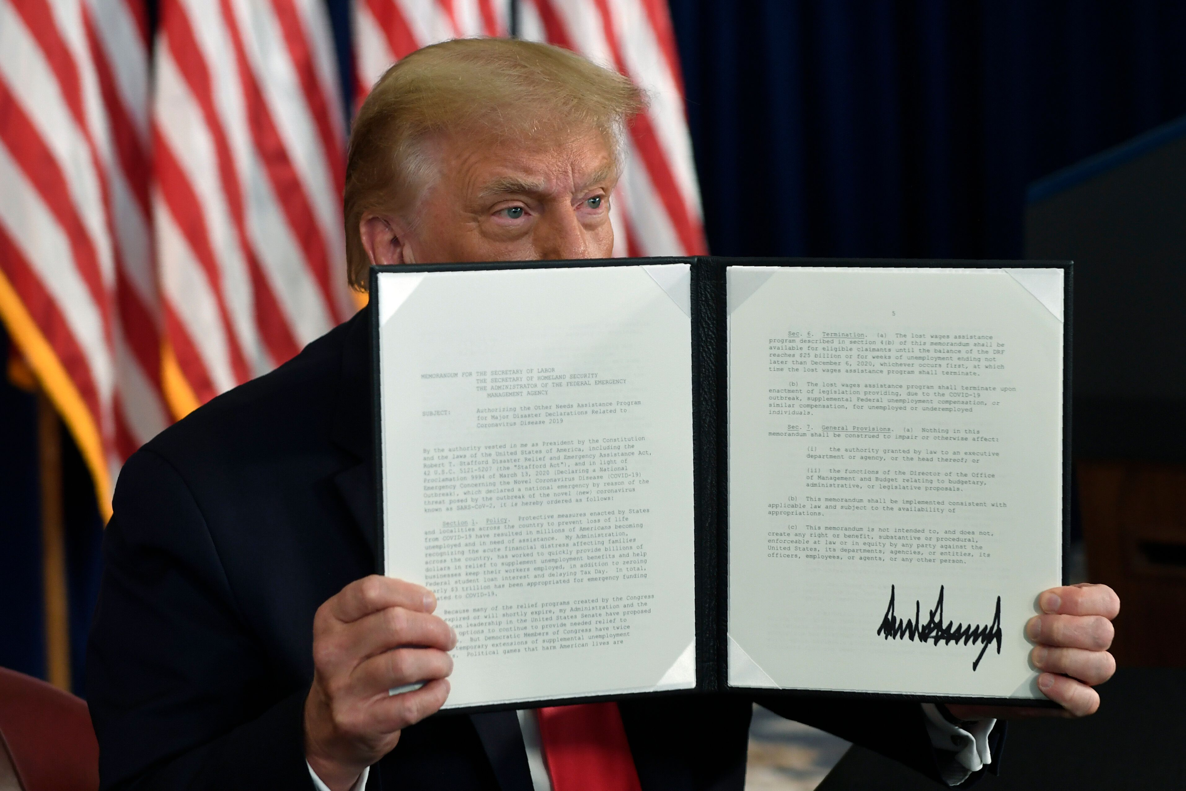 President Donald Trump signs an executive order during a news conference at the Trump National Golf Club in Bedminster, New J