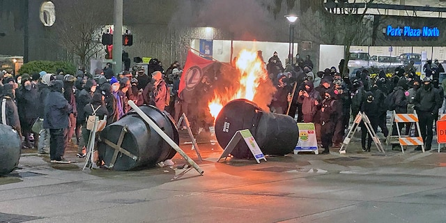 Antifa activists, dressed in black bloc, set small fires in an intersection by Frost Park in Tacoma, Wash. before their destructive march.