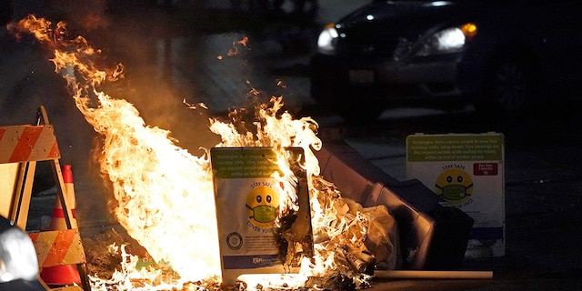 A car drives near burning trash and a COVID-19 mask safety sign during a protest against police brutality, late Sunday, Jan. 24, 2021, in downtown Tacoma, Wash., south of Seattle. (AP Photo/Ted S. Warren)