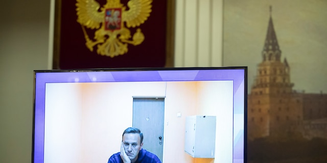 Russian opposition leader Alexei Navalny appears on a TV screen during a live session with the court during a hearing of his appeal, in Moscow, Russia, Thursday, Jan. 28, 2021. Navalny was jailed soon after arriving to Moscow after authorities accused him of violating of the terms of his 2014 fraud conviction. A court on Thursday is to hear an appeal on the ruling to remand him into custody. Next week, another court will decide whether to send him to prison for several years for the alleged violations. (AP Photo/Pavel Golovkin)