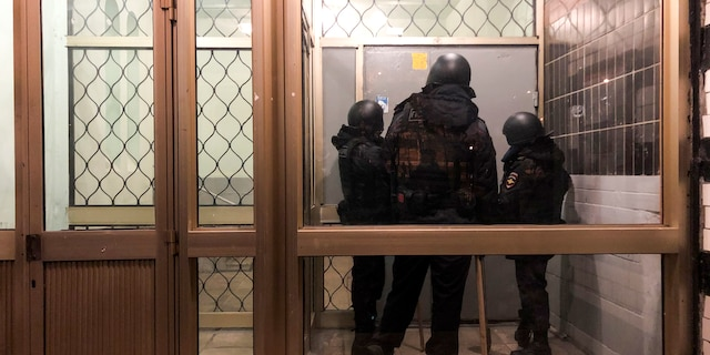 Police stand in front of a door of the apartment building where Oleg Navalny, brother of jailed opposition leader Alexei Navalny lives in Moscow, Russia, Wednesday, Jan. 27, 2021. Police are searching the Moscow apartment of jailed Russian opposition leader Alexei Navalny, another apartment where his wife is living and two offices of his anti-corruption organization. Navalny's aides reported the Wednesday raids on social media. (AP Photo/Mstyslav Chernov)