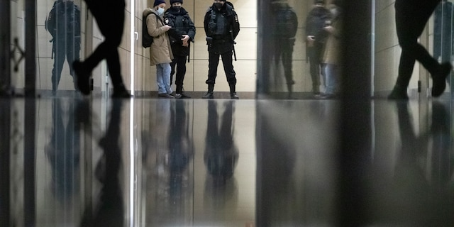Police stand guard at the Foundation for Fighting Corruption office in Moscow, Russia, Wednesday, Jan. 27, 2021. Police are searching the Moscow apartment of jailed Russian opposition leader Alexei Navalny, another apartment where his wife is living and two offices of his anti-corruption organization. Navalny's aides reported the Wednesday raids on social media. (AP Photo/Pavel Golovkin)