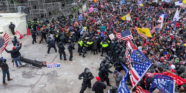 WASHINGTON DC, DISTRICT OF COLUMBIA, UNITED STATES - 2021/01/06: Pro-Trump protesters and police clash on top of the Capitol building. Rioters broke windows and breached the Capitol building in an attempt to overthrow the results of the 2020 election. Police used batons and tear gas grenades to eventually disperse the crowd. Rioters used metal bars and tear gas as well against the police. (Photo by Lev Radin/Pacific Press/LightRocket via Getty Images)