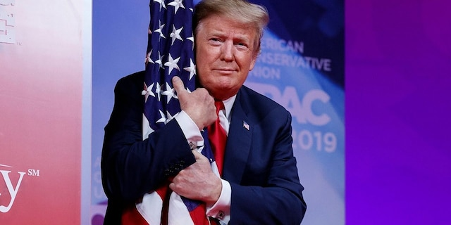 President Donald Trump hugs the American flag as he arrives to speak at the Conservative Political Action Conference, CPAC 2019, in Oxon Hill, Md., on March 2, 2019. (AP Photo/Carolyn Kaster)