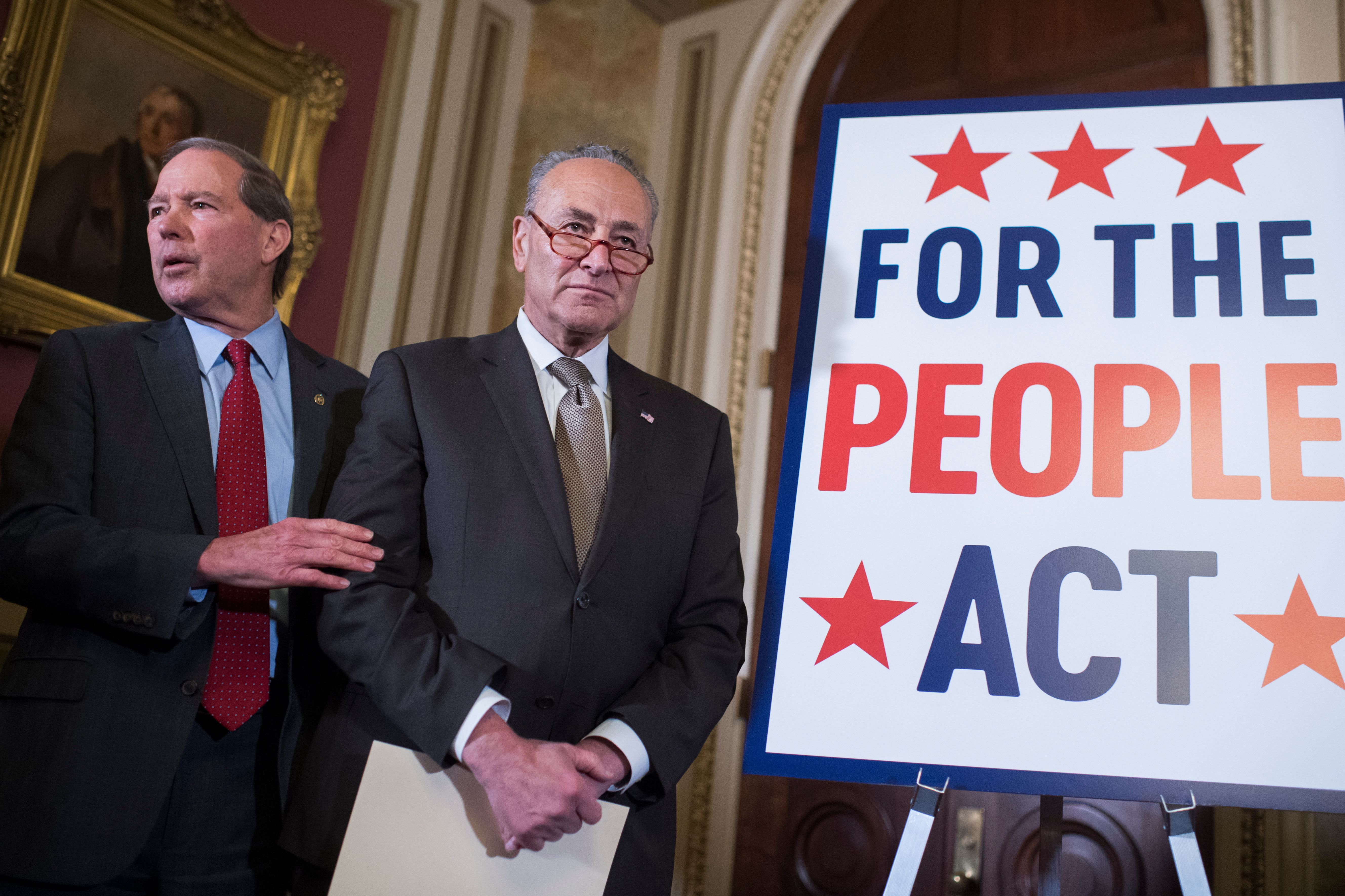 Then-Senate Minority Leader Charles Schumer (center) and then-Sen. Tom Udall (D-N.M.) attend a news conference about the For