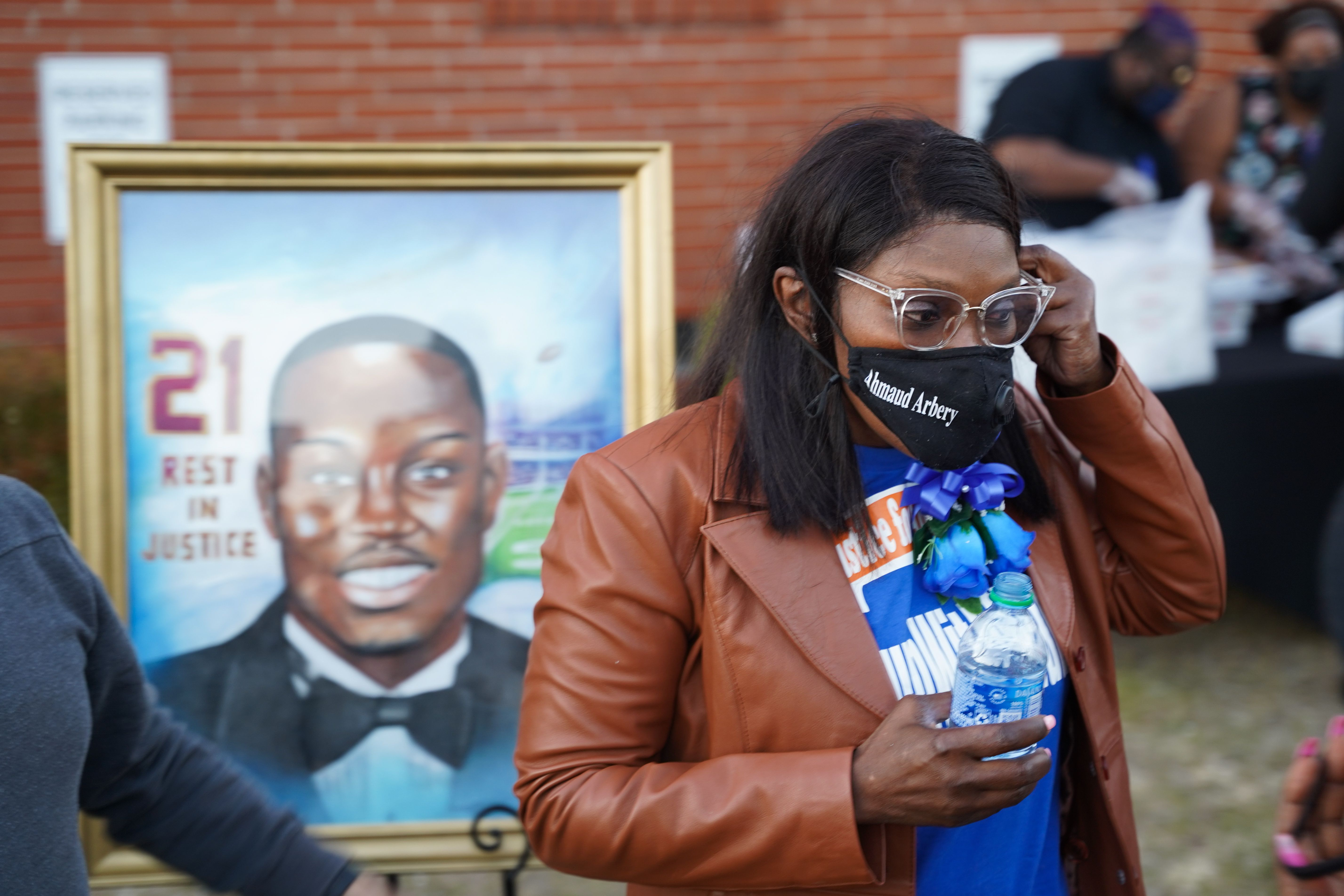 Wanda Cooper-Jones, the mother of Ahmaud Arbery, stands in front of a painting of her son after a candlelight vigil for him o