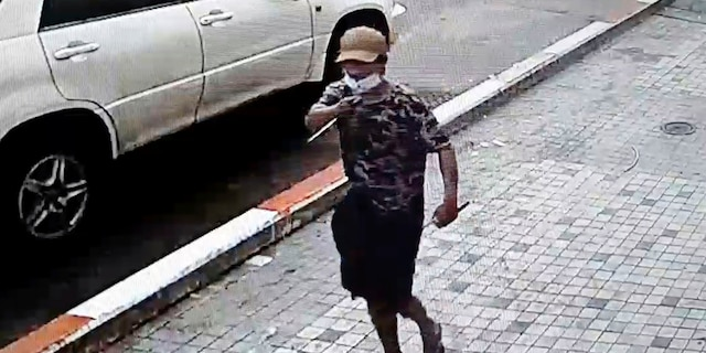 In this image taken from video obtained by Than Lwin Khet News, a man holds a pointed instrument before he attacks an unidentified man on the sidewalk of Sule Pagoda Road in Yangon, Burma, on Thursday. (Than Lwin Thet News via AP)