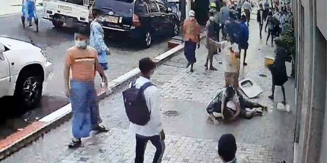 In this image taken from video obtained by Than Lwin Khet News, a woman helps an unidentified man lying on the sidewalk of Sule Pagoda Road after he was attacked by a group of men in Yangon, Burma, on Thursday. (Than Lwin Thet News via AP)
