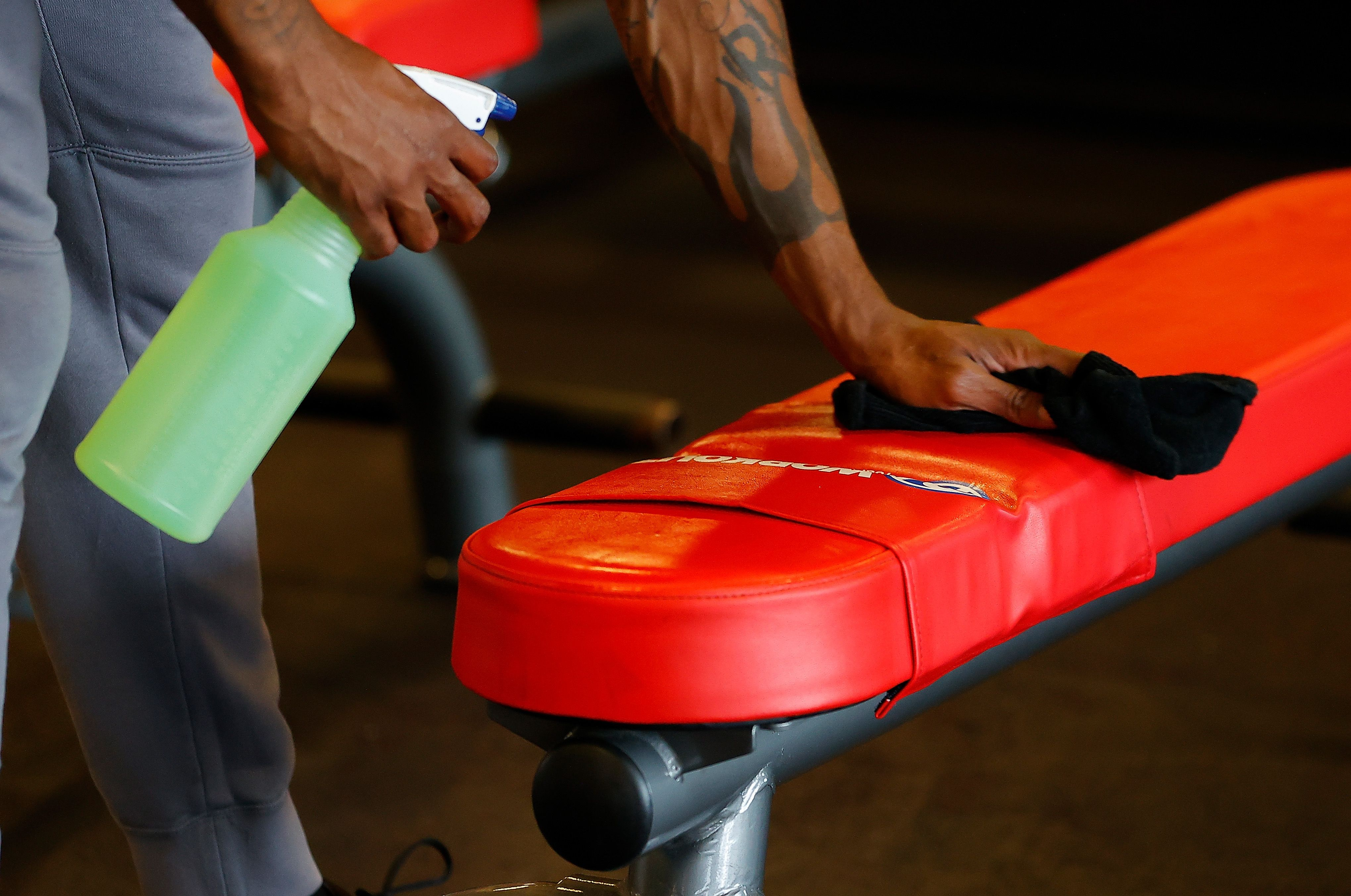 Army Vet Valentino Murray cleans a bench before using it at Workout Anytime Powder Springs gym on April 24, 2020, in Powder S