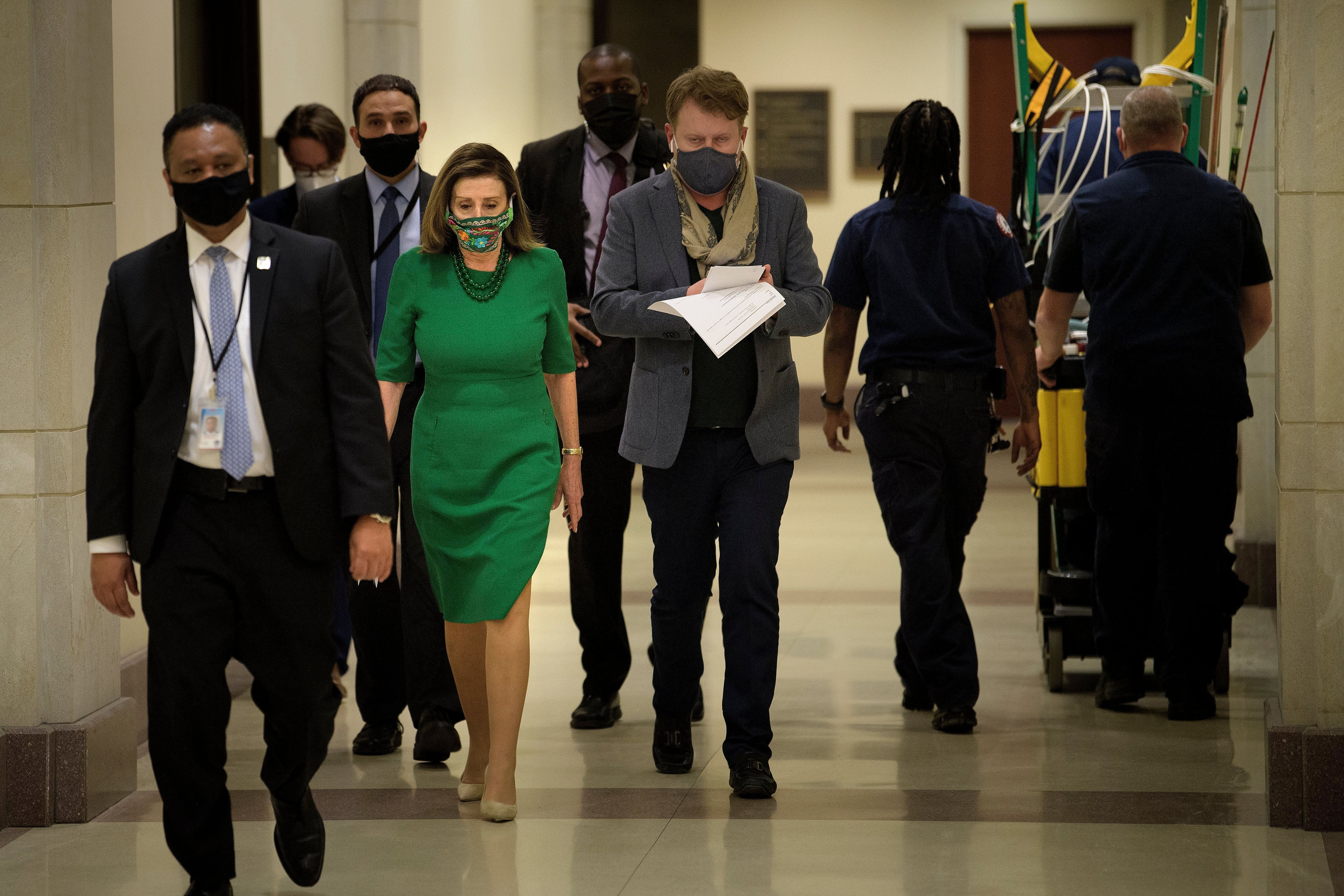 Speaker of the House Nancy Pelosi (D-Calif.) walks to a news conference Friday about the COVID-19 financial relief package an