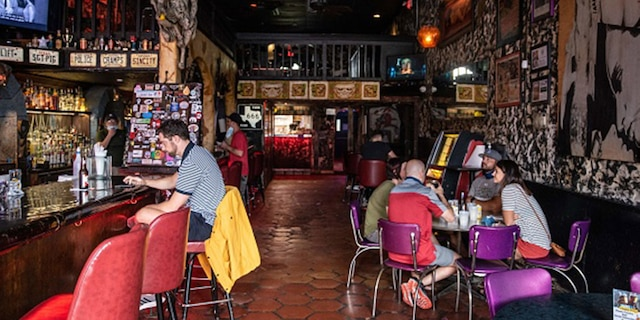 People sit at the bar of a restaurant in Austin, Texas, June 26, 2020. (Photo by Sergio FLORES / AFP)