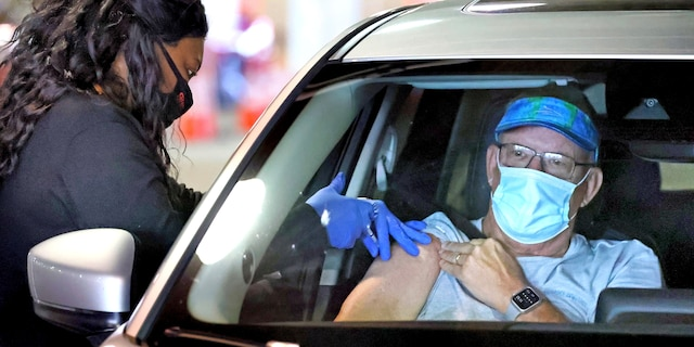 A Florida resident gets vaccinated at the drive-thru site at the Orange County Convention Center in Orlando, Monday, Feb. 22, 2021. (Joe Burbank/Orlando Sentinel via AP)