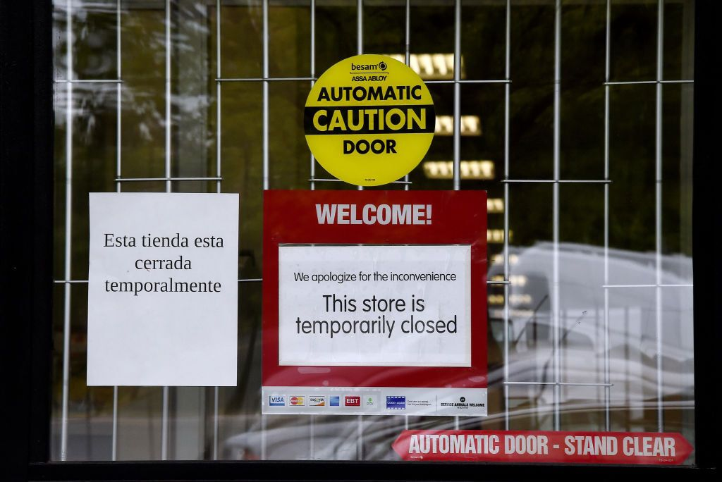 """A sign """"Temporarily Closed"""" is seen in front of a store amid the coronavirus pandemic on May 14, 2020, in Arlington, Virginia"""