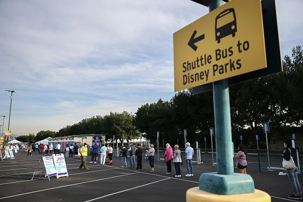 People wait in line to receive the COVID-19 vaccine at a mass vaccination site in a parking lot for Disneyland Resort on Janu