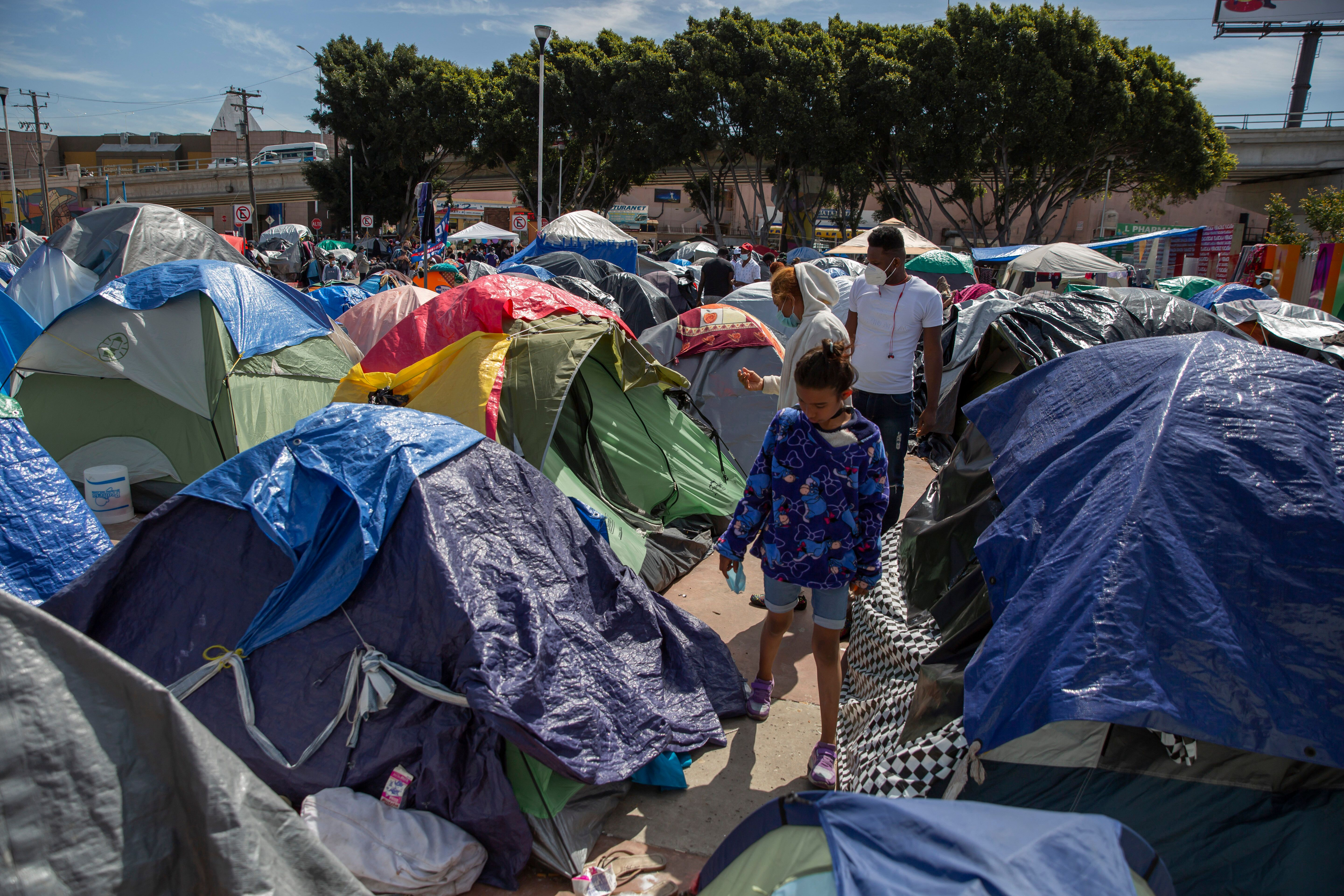"""A child walks through tents at a migrant camp on the grounds of the National Institute for Migration near the """"El Chaparral"""""""