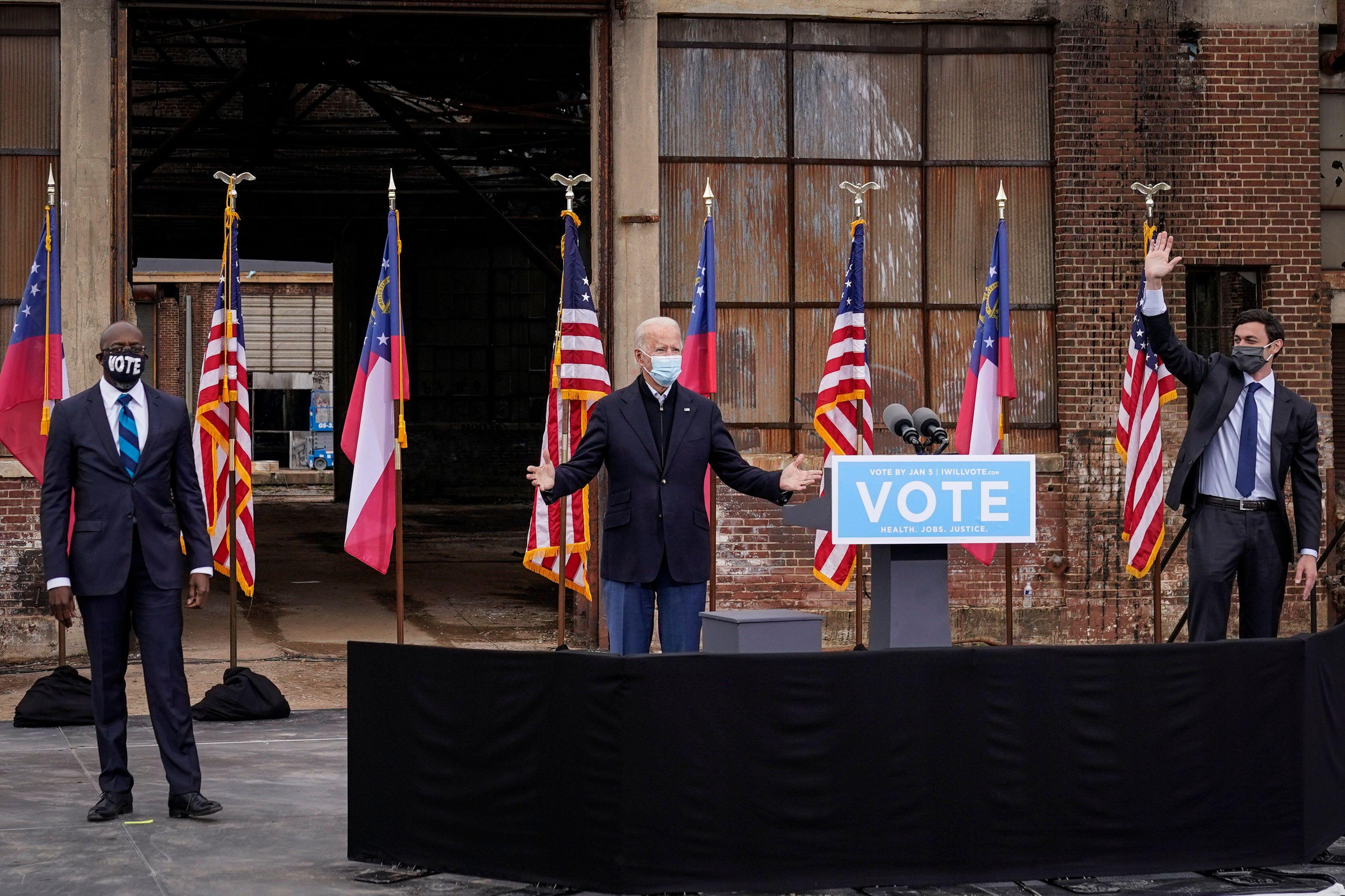 Flanked by U.S. Democratic Senate candidates Rev. Raphael Warnock (left) and Jon Ossoff (right), President-elect Joe Biden ge