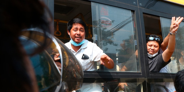 An arrested protester flashes the three-fingered salute while onboard a bus getting out of Insein prison to go to an undisclosed location Wednesday, March 24, 2021 in Yangon, Burma. (AP Photo)