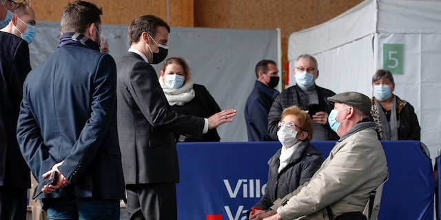 French President Emmanuel Macron talks to elderly people after they received a Pfizer COVID-19 vaccine at the vaccination center of Valenciennes, northern France, Tuesday, March 23, 2021. The French government has backed off from ordering a tough lockdown for Paris and several other regions despite an increasingly alarming situation at hospitals with a rise in the number of COVID-19 patients. (Yoan Valat/Pool Photo via AP)