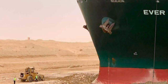 In this photo released by the Suez Canal Authority, a cargo ship, named the Ever Green, sits with its bow stuck into the wall Wednesday, March 24, 2021. (Suez Canal Authority via AP)